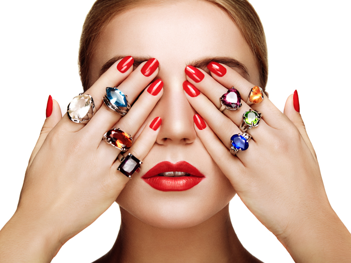 Jewelry photo of woman covering her eyes with her hands, wearing colourful rings on every finger