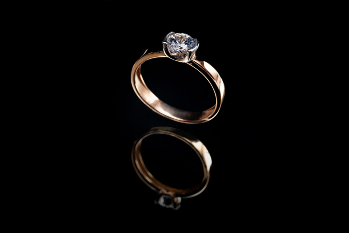 Jewelry product photo of a gold engagement ring on black background, and its reflection