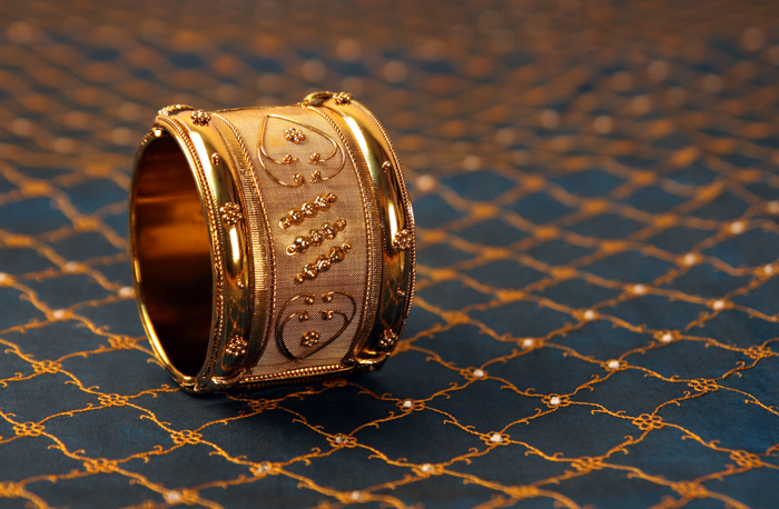 a gold bracelet on blue and golden fabric