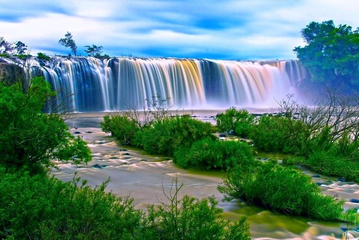 long-exposure image of flowing waterfalls in a lake