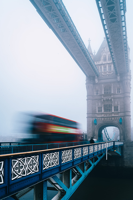 A blurred bus moving over a bridge