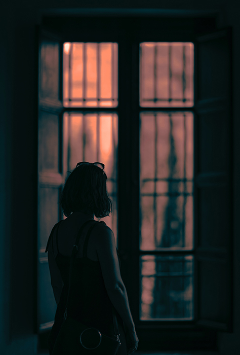 Moody scene of a girl looking out a window in a dark room