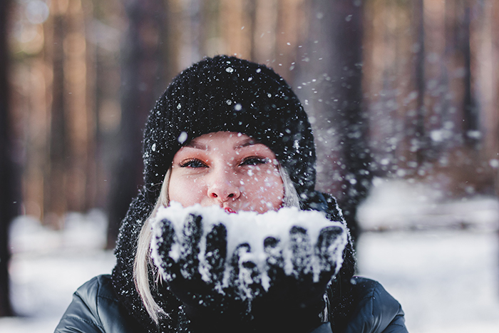 photo of a woman playing with the snow