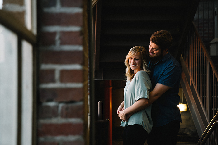 photo of a couple hugginf each other under a stairway