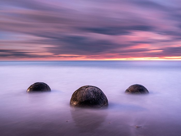boulders in the sea under a long-exposure sky