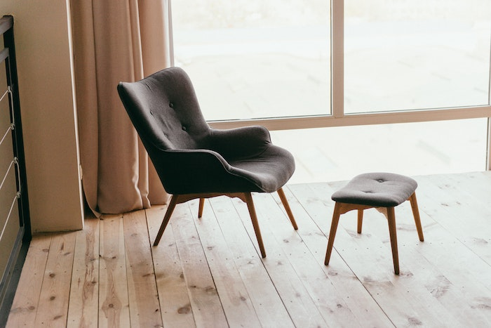 A grey chair and stool indoors
