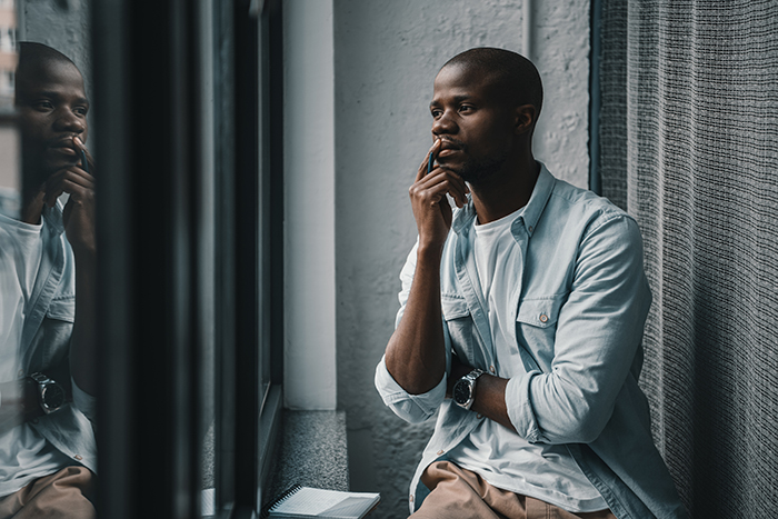 Portrait of young thoughtful man looking out the window.