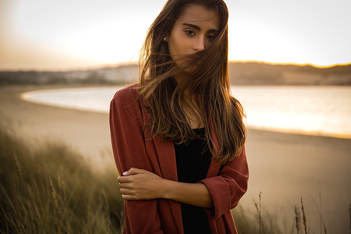 Portrait of a beautiful woman on the beach during golden hour.
