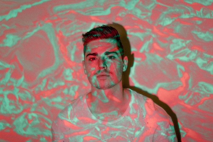 A portrait of a man with a projected photo of abstract colors over him