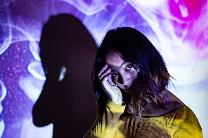 A portrait of a female model with a projected photo of colorful smoke on her