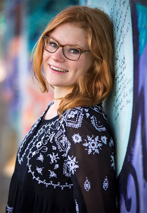 Portrait of a woman with glasses smiling and leaning against a wall