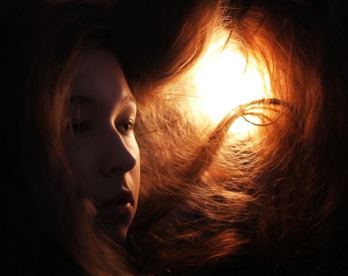 Portrait photo of a girl with red hair in tungsten light