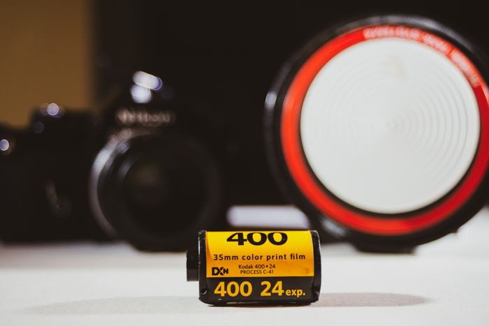 A close up of a roll of film with camera in the background