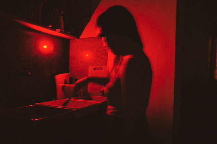 A girl developing film in a DIY darkroom