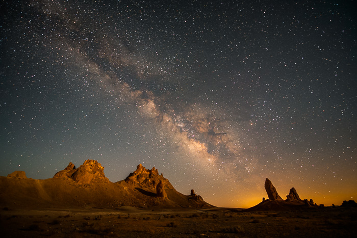 Night photo of the Milky Way appearing above mountains