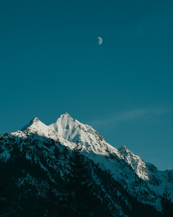 A sharp photo of a mountain with the half Moon on the sky above