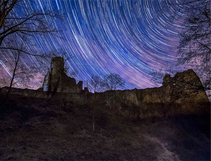 Star trails over a stone ruin