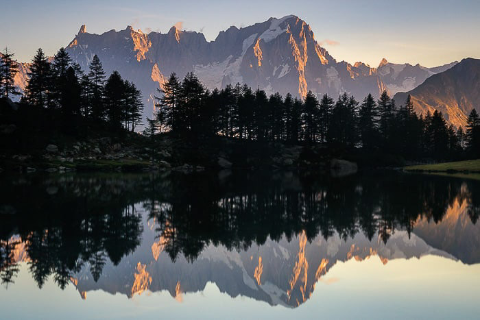 Beautiful long exposure of trees and mountains reflecting in a lake