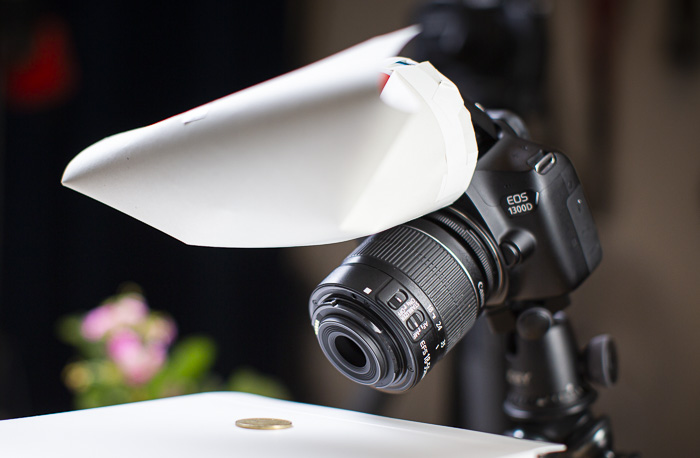 A DSLR taking a photo of a coin with a DIY photography lighting flash diffuser attached