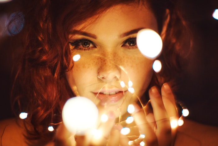 A female model holding fairy lights as DiY photography lighting