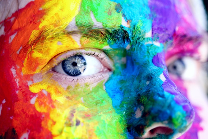 A close up of a persons face covered in colored Holi powder