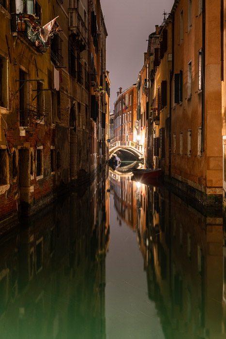 Broad scene of Venetian bridge and canal at night.