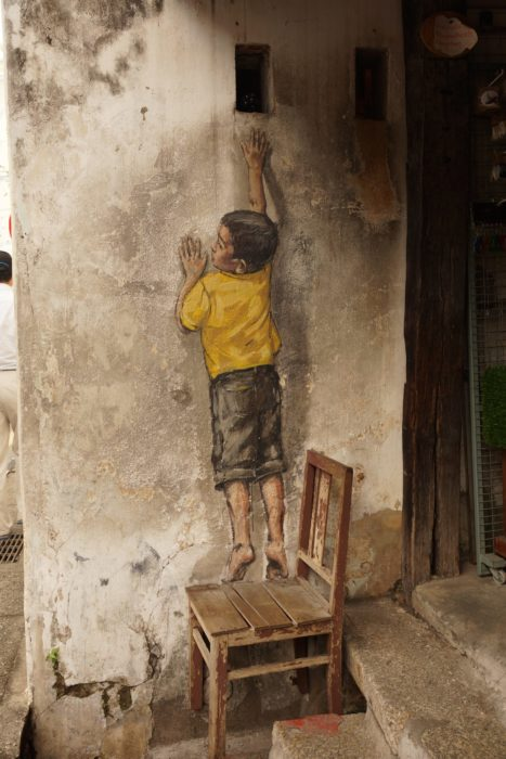 Painting of a boy on a wall with a chair under his feet