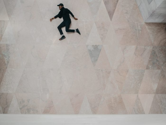 Photo of a guy seemingly jumping with a marble floor background
