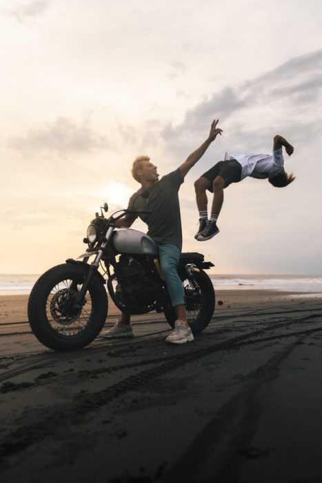 Photo of a guy on a motorcycle with a boy jumping from it