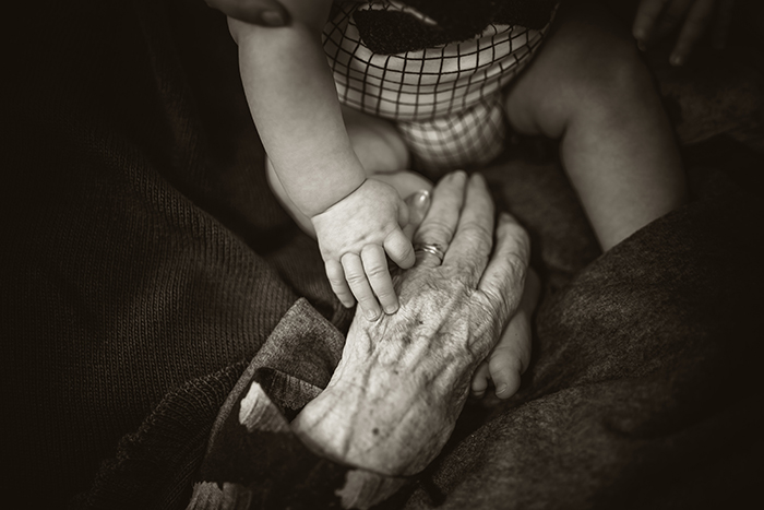 A babys hand touching an old person hands