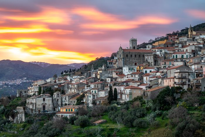 photo of a small village on a hill at sunset