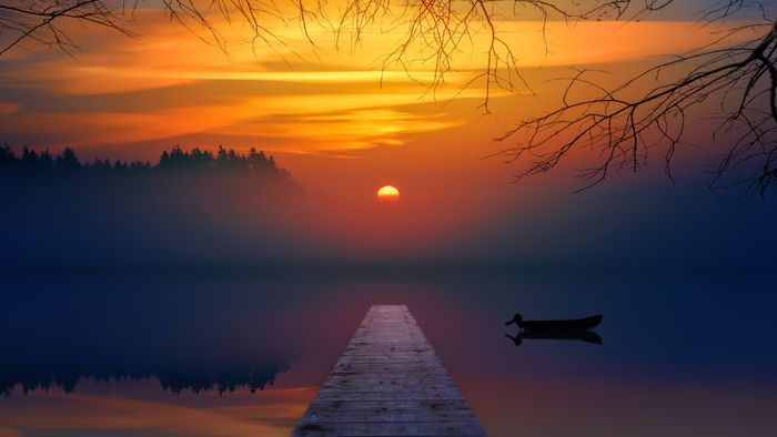 photo of a pier leading into the sunset over a lake
