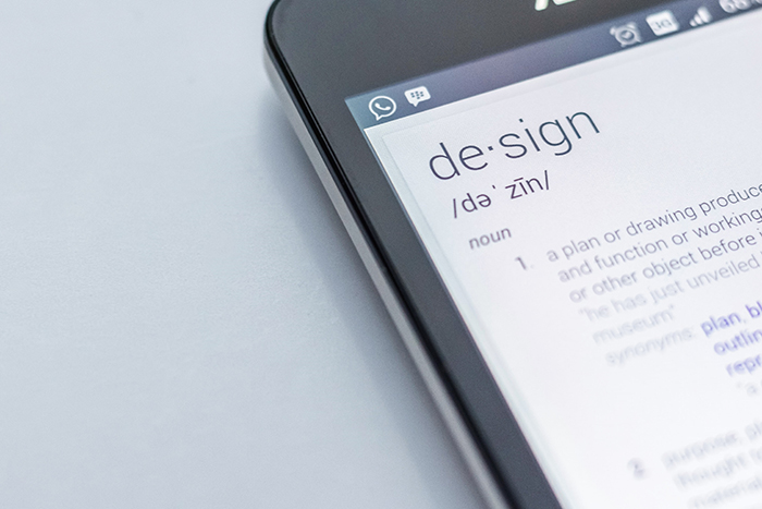 A close up of a smartphone opened on a thesaurus page for the word design