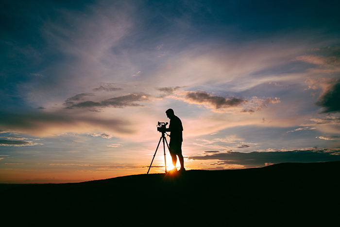 A photographer taking a landscape shot at evening time