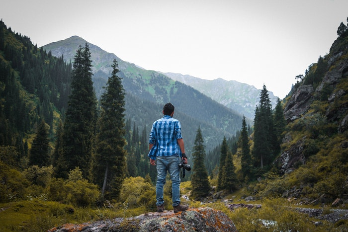 A wildlife photographer stands in the wilderness