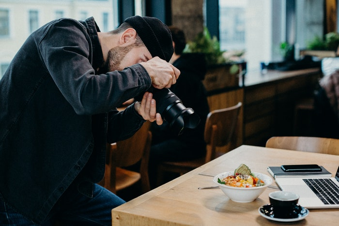 A man taking a food photo in a restaurant