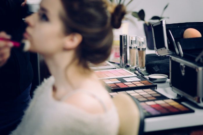 A model getting her make up done before a shoot
