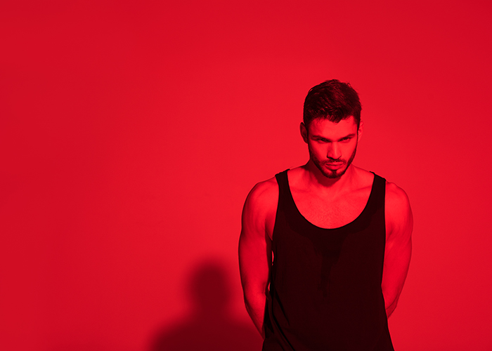 Young man under contrasty red light.