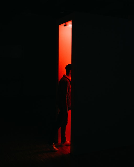 A man walking into a photography darkroom