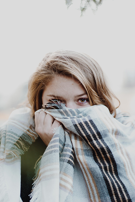 Girl hiding her face in a scarf