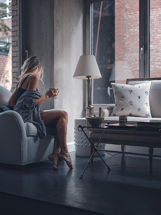 Blonde girl drinking coffee in a living room