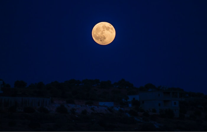 Photo of the full moon above a town at night