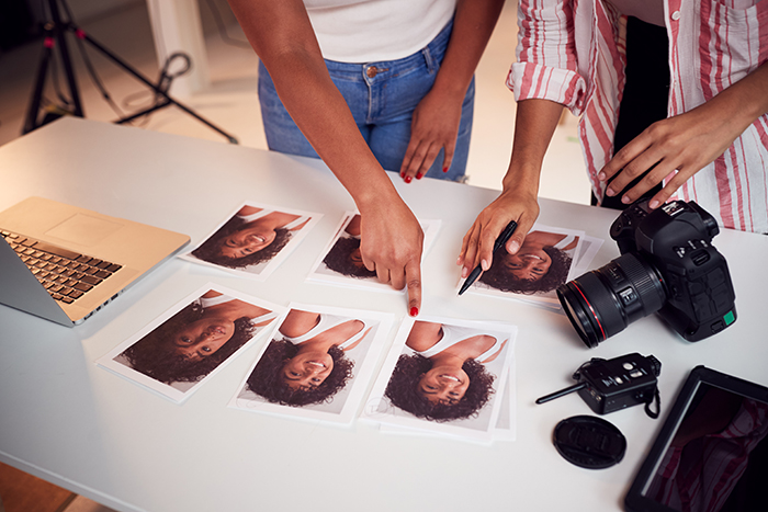 Detail Of Photographer With Female Client Editing Images.