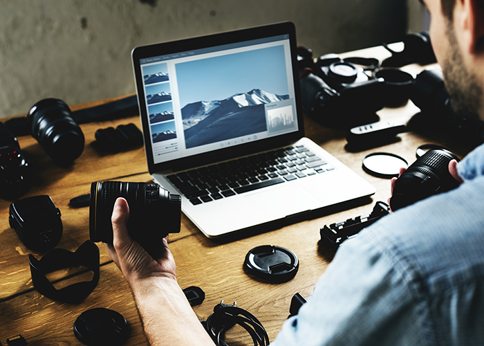Photographer editing on his desktop with full of cameras.