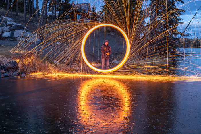 Steel wool photography with a man stanting in the middle of the circle