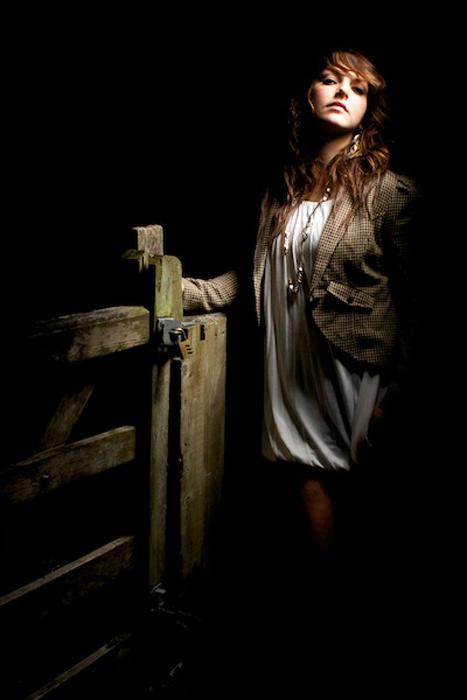 A woman posing in a barn in low light