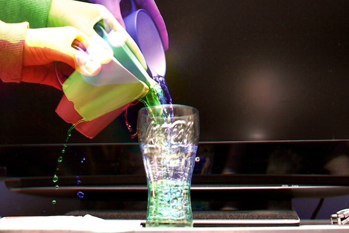 Harris effect of colorful hands pouring colorful water into a glass