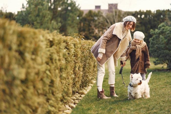 Mãe e filha passeando com um cachorro pequeno