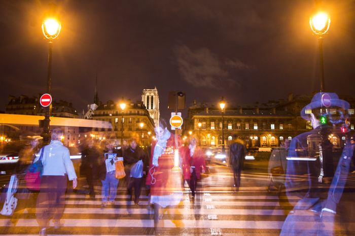 People crossing the zebra at night. They are blurred.