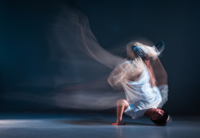 Break dancer during movement, standing on his head, with a dark background behind him.